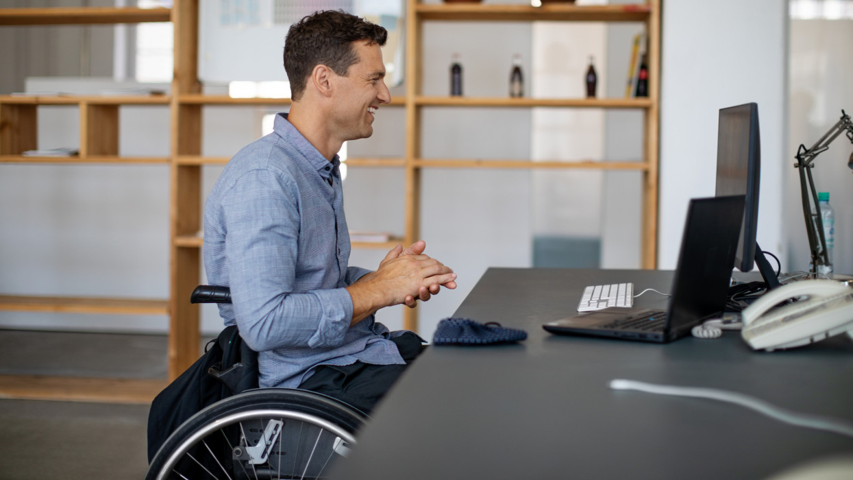 Side view of a businessman with disability in wheelchair having a video conference meetting. Businessman smiling during online web conference at office desk.
