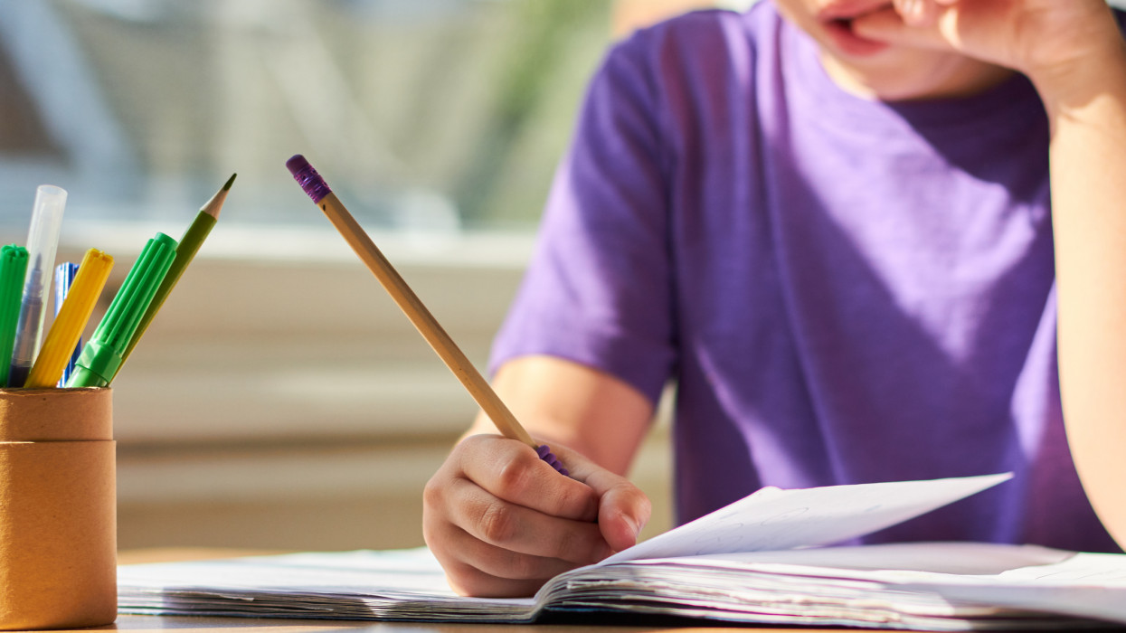 Young child sitting at a table learning and completing school work.