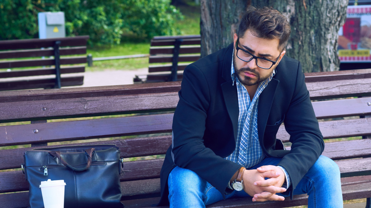 Young man with sad facial expression sitting on a bench in the park. Office worker lost his job. Middle aged man despair economic crisis. jobless cimlapi