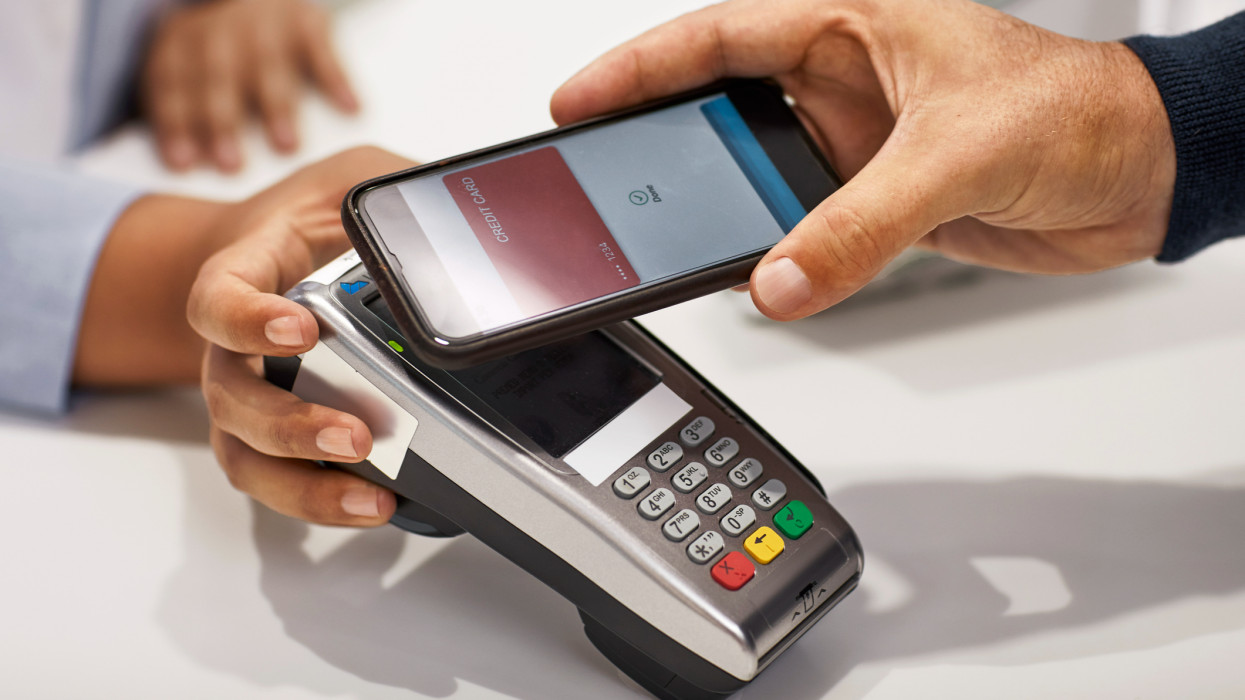 Cropped image of man using contactless payment in medical store. Hands of cashier and customer holding technologies. They are at checkout counter.