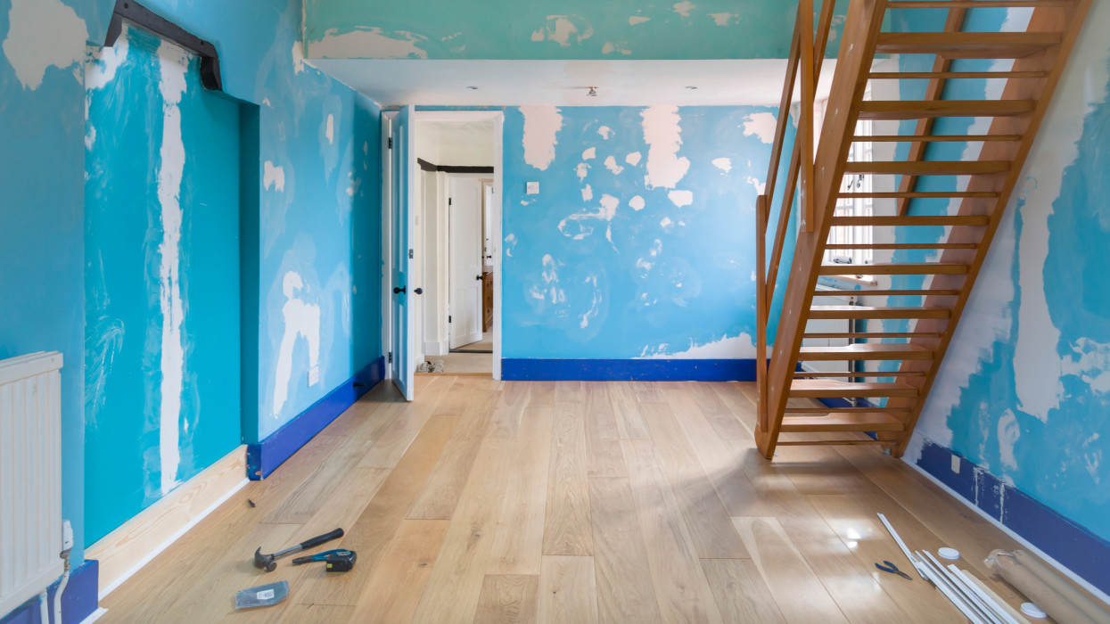 Room home improvement with a new wooden floor and walls prepared for painting