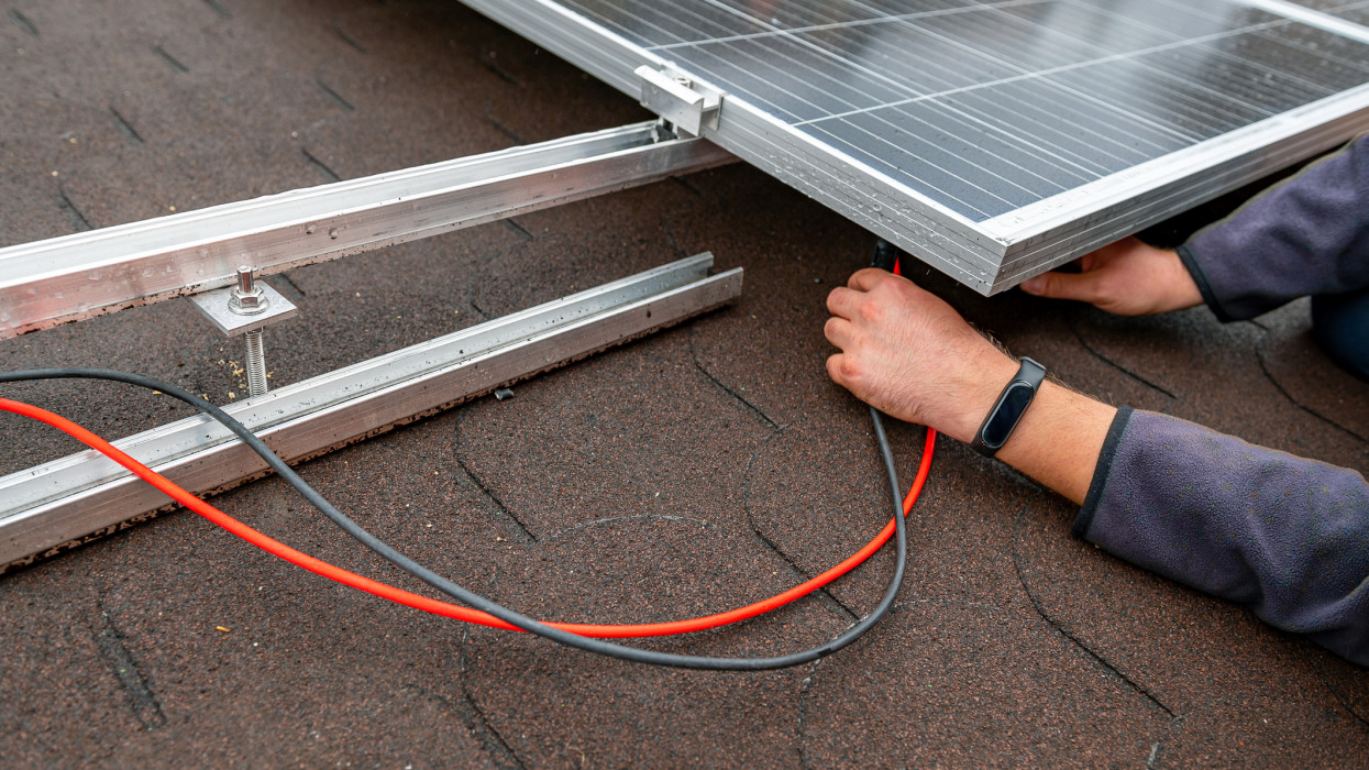Photovoltaic skilled worker wiring solar panels on the roof