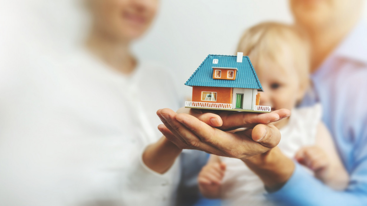 new family home concept - young parents and child with dream house scale model in hands. copy space