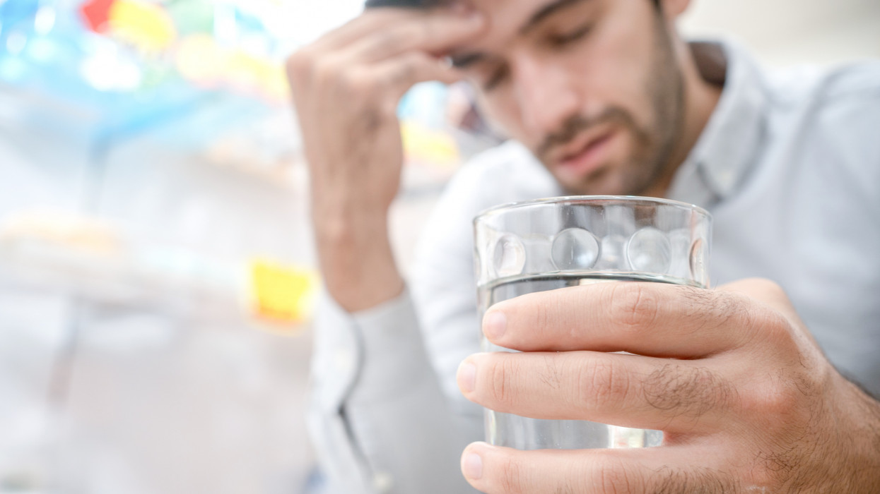 Young man suffering from strong headache or migraine sitting with glass of water in the kitchen, millennial guy feeling intoxication and pain touching aching head, morning after hangover concep