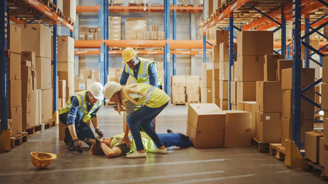 Warehouse Worker Has Work Related Accident Falls while Trying to Pick Up Cardboard Box from the Shelf. Colleagues Call for Help and Medical Assistance. Injury at Work.